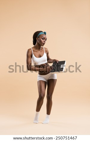 Sexy fit african woman posing with scales. Perfect Figure. Weight Loss Concept - stock photo