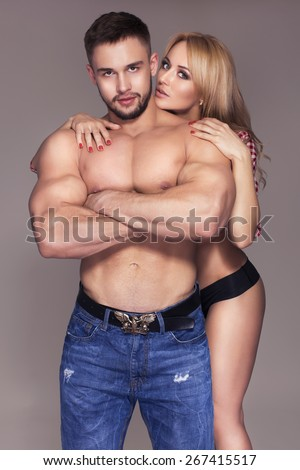 Sexy fit muscled couple in jeans and pants and plaid t-shirt on neutral grey background hugging - stock photo