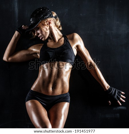 Sexy fit woman in a cap posing on dark background - stock photo