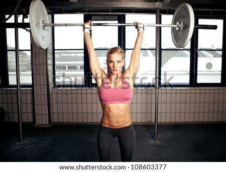Sexy fit woman performing a shoulder press exercise - stock photo