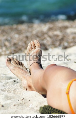Sexy foot of a woman with an anklet relaxing on the beach - stock photo