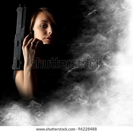 Sexy girl holding gun with smoke - stock photo