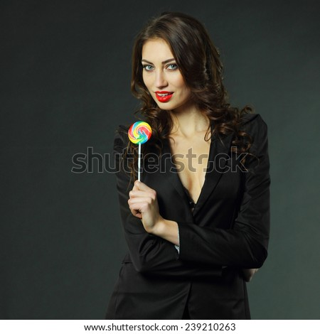 sexy girl in a jacket, stockings and bra sucks a lollipop. - stock photo