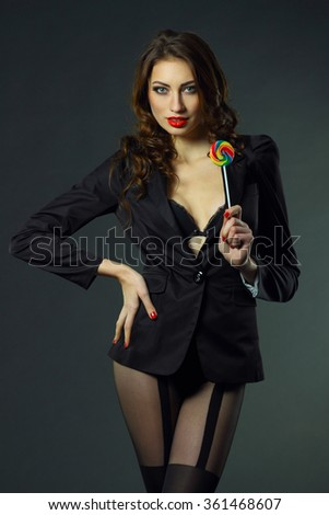 sexy girl in a jacket, stockings and bra sucks a lollipop - stock photo
