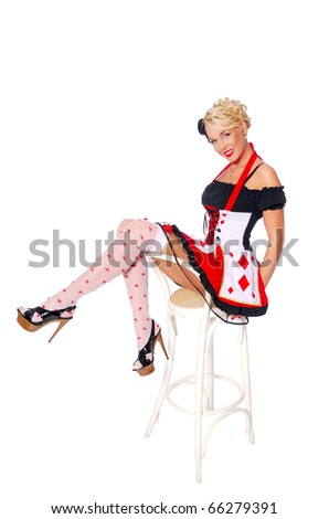 Sexy girl in a queen of hearts costume sit on the chair and show long legs - stock photo