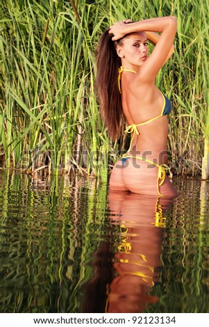 Sexy girl in bikini posing at sunset - stock photo