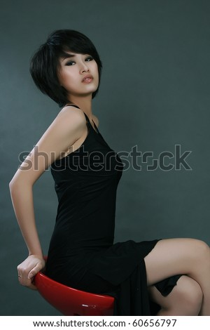 Sexy girl in black skirt sitting on chair - stock photo