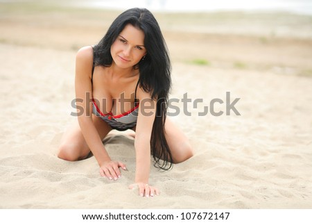 sexy girl in the sand, kneels - stock photo