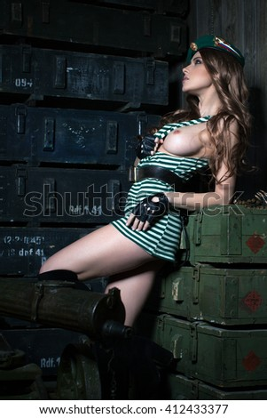 Sexy girl in uniform border troops. It stands next to the machine gun - stock photo