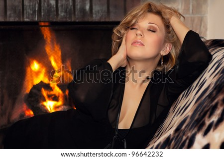 Sexy girl lying by the fireplace in the new year - stock photo