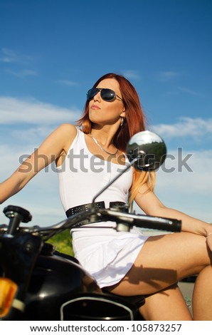 Sexy girl on a motorbike on a sky background - stock photo
