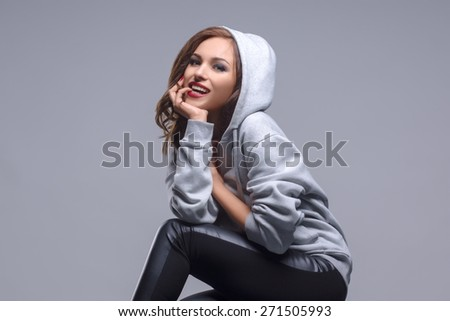 Sexy girl posing and smiling in a studio in sports sweatshirt - stock photo