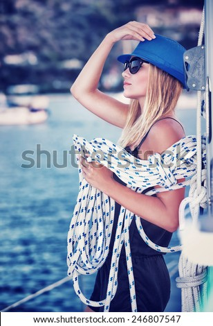 Sexy girl standing on sailboat with rope, vintage style photo of attractive sailor girl, active lifestyle, summer vacation concept - stock photo
