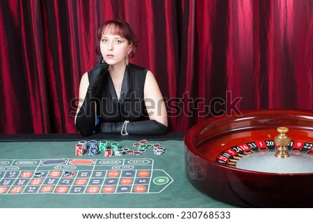 sexy girl wearing black dress and gloves plays in casino - stock photo