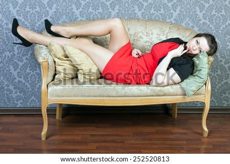 sexy girl wearing red dress lies on a sofa - stock photo