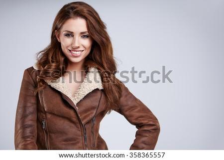 Sexy girl wearing winter fur jacket  posing over grey - stock photo