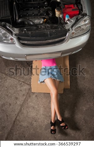 Sexy girl with long legs lying under car checking the engine at the car repair shop. Wearing blue jeans skirt and pink top. View from the top - stock photo