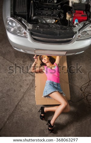 Sexy girl with long legs lying under car checking the engine with constant light at the car repair shop. Wearing high heels blue jeans skirt and pink top. View from the top - stock photo