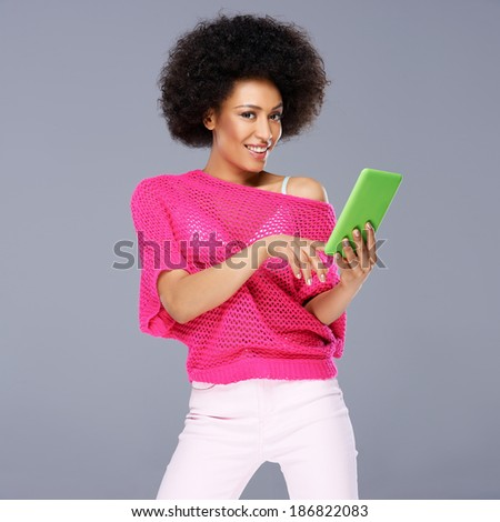 Sexy glamorous beautiful African American woman in a stylish pink top holding a tablet in her hand as she smiles provocatively at the camera - stock photo