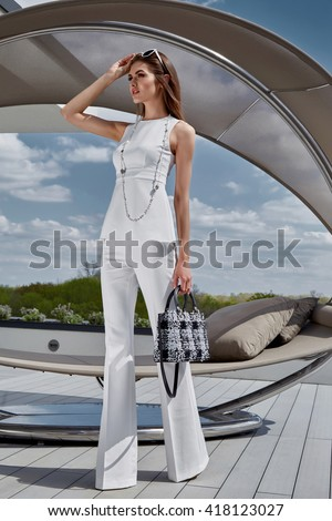 Sexy glamour beautiful fashion model lady woman wear stylish costume silk blouse pants accessory bag summer collection clothes party luxury life style street look brunet hair makeup natural sunglasses - stock photo