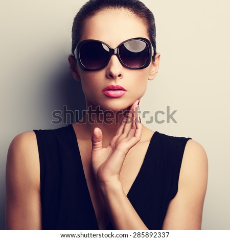Sexy glamour female model in trendy sun glasses with hand at face. Closeup vintage portrait - stock photo