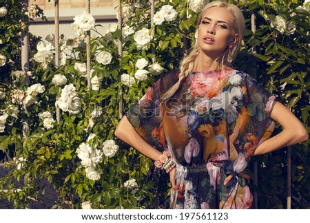 sexy glamour woman with blond hair in colorful dress posing at summer park beside a rosebush - stock photo