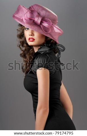 Sexy goddess. A portrait of a sexy brunette wearing a black retro dress and a rosy designer hat. - stock photo