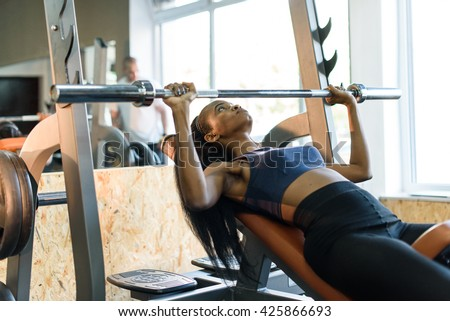 Sexy gorgeous african american woman training with barbell at the gym - stock photo