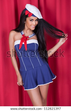 Sexy gorgeous woman in cute nautical outfit with miniskirt and beret posing on a stage against red curtains - stock photo