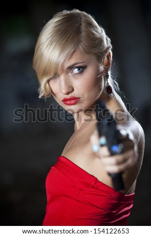 Sexy gun woman in retro look pointing gun - stock photo