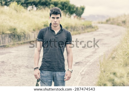 Sexy handsome young man in jeans and black t-shirt walking along rural road - stock photo