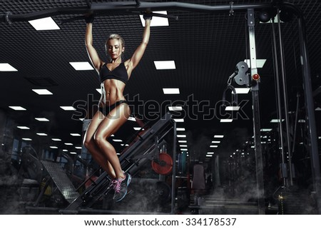 Sexy hot blonde fitness bikini girl with perfect shape body making elevations pull up in gym - stock photo