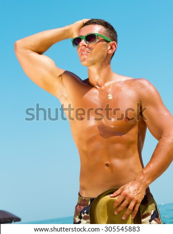 Sexy hot muscular Man on beach wearing hipster hat, sunglasses,military printed trousers.Young male model enjoying beach. - stock photo