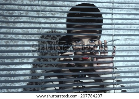 sexy jalousie woman with vintage style looking through shutters of the window and talking on retro telephone - stock photo