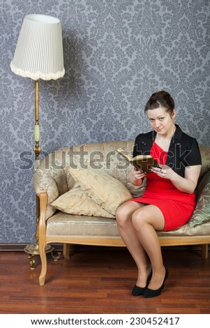 sexy lass sits on a sofa and reads a book - stock photo