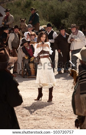 Sexy Latina woman in western outfit with pistol - stock photo
