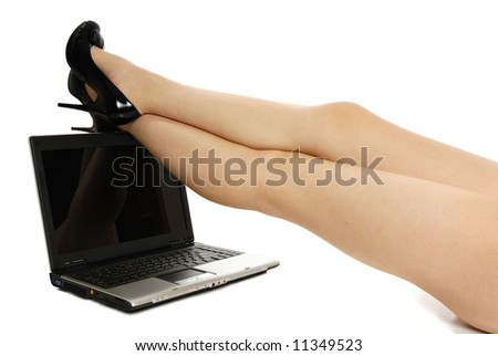 sexy legs over laptop isolated on white - stock photo
