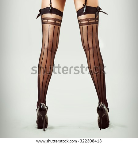 Sexy long legs in stockings of beautiful slender woman - stock photo