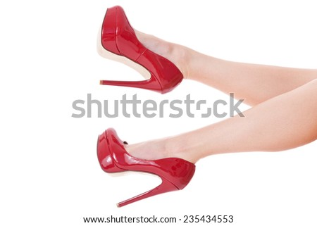 Sexy long shapely bare female legs in elegant red stilettos kicking tantalizingly in the air in a provocative gesture, isolated on white - stock photo
