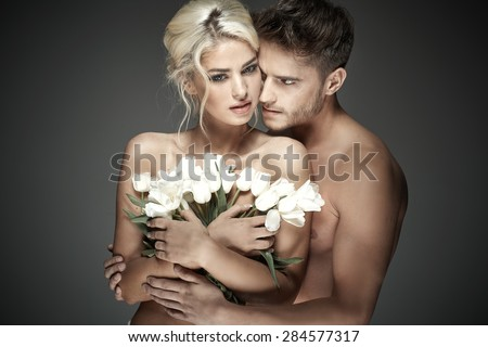 Sexy loving couple with flowers - stock photo