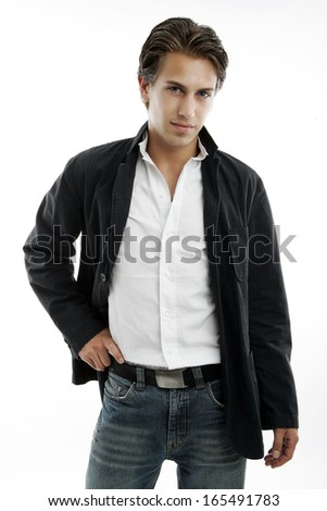 Sexy macho handsome young man in trendy jeans and jacket standing with a confident pose and his hand on his hip, three quarter on white - stock photo