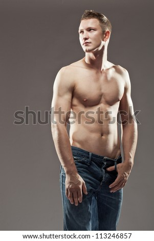 Sexy macho shirtless man with a muscular body posing in jeans with his one thumb hooked in the belt loops - stock photo