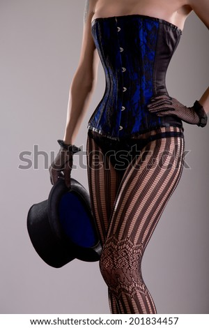 Sexy magician girl in corset and lingerie holding top hat, studio shot  - stock photo
