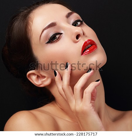 Sexy makeup female glamour model with red lipstick and black polish finger nails on black background. Closeup - stock photo