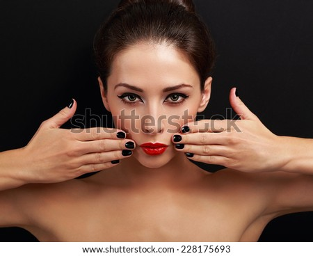 Sexy makeup female model with black nails polish looking serious on black background - stock photo