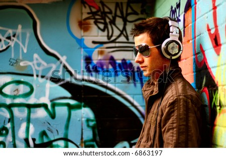 Sexy male DJ pose infront of graffiti - stock photo
