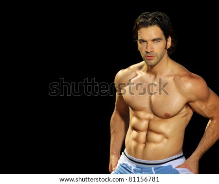 Sexy male fitness model on black background with lots of copy space - stock photo