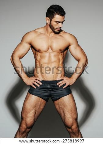Sexy male muscular model in black swimwear looking down - stock photo