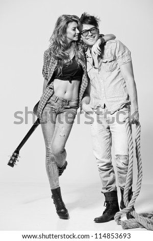 Sexy man and woman doing a fashion photo shoot in a professional studio - bw retro mood - stock photo