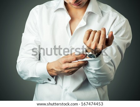 Sexy man buttons cuff-link on French cuffs sleeves luxury white shirt - stock photo
